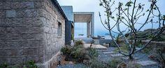 K domečkům přibyla puristická betonová přístavba se střešní terasou s perfektním výhledem na moře.