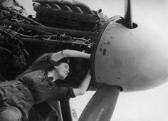Women's Auxiliary Air Force plane mechanic checking wiring of a Mosquito engine.