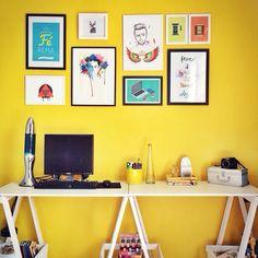 Parede amarela, cavaletes e quadros <3