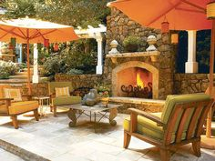 a tiled outdoor space with two large umbrellas over deck chairs and a fireplace