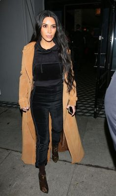 With Two Styling Tricks, Kim Kardashian Takes a Tracksuit for a Night on the Town Kim Kardashian is one of our street style stars! We love these amazing and effortless fashion moments. For dinner with sister Kourtney, she wore an all-black tracksuit (fit is key) topped with a beige duster and pointy boots.
