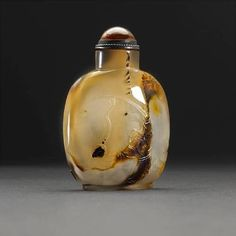 A silhouette agate snuff bottle, 1820-1900. Photo Bonhams Of flattened ovoid form with slightly concave mouth and slightly recessed oval foot surrounded by an short oval footrim, the well hollowed, translucent body with dark brown striations incorporating the design of two playful boys fishing and holding a giant basket; 2 3/8in (6cm) high. Estimate: US$2,500 - 4,000