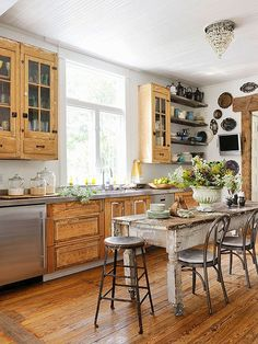 Stripped cabinets, a doorway trimmed in reclaimed lumber, and floors seemingly scuffed over generations bring a primitive feel to a kitchen equipped with modern stainless-steel appliances and countertops. A crystal fixture, shapely urn, and tarnished silver serving pieces elegantly counterbalance the room's time-battered furnishings and finishes./
