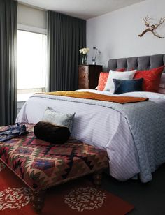 Love the mixture of eclectic elements. Cool tribal fabric on ottoman at the end of the bed. Great gray tufted headboard and fun mixture of colored pillows