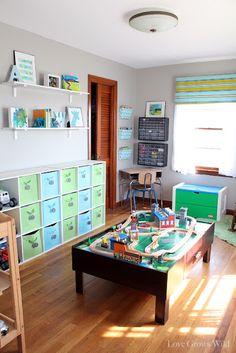 I love absolutely everything about this playroom!!!! modular toy storage, craft/Lego corner with magazine shelves for coloring books and tool drawers for craft things, reading nook, changing table to park big trucks, plus cute wall decor. Love love love!
