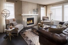 Sierra Showhome in New Brighton, Calgary - a light stone fireplace with tan walls and dark hardwood floors, brown furnishings and cream drapes all come together to create a rich liveable space