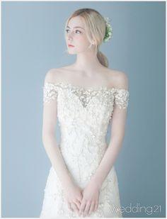 유려하고 우아한 드레스의 향연. 로맨틱 웨딩 세리머니를 위한 제이미브라이드의 웨딩 신. Designed by Jaymibride리본 장식이 사랑스러운 머메이드 드레스. 러플 디테일의 스커트가 신비로운 브라이덜 룩을 완성한다.얼굴이 작아 보이는 보트네크라인 드레스가 세련미를 더한다. 시스루 슬리브의 레이스 디테일이 우아함을 배가한다.꽃잎이 흩날리는 듯한 비딩으로 수놓은 오프숄더 …