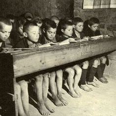 Greece, 1942-1944. Students at an elementary school; a galloping inflation imposed by the German authorities paying for goods on the Greek market with counterfeit money, made an unaffordable luxury the buy of new shows, especially for growing children.