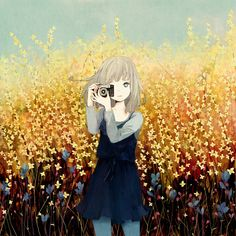 A green eyed girl with a camera in a field of yellow wild flowers
