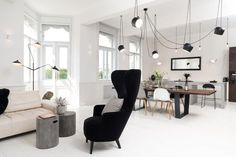 A large black chair makes a statement in this spacious sunlit interior along with AIM pendant lights.