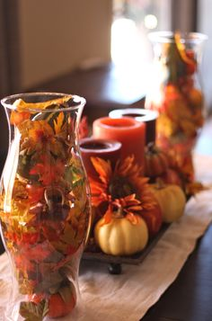 $.99 glass hurricanes from #Goodwill filled with faux leaves for a simple #Thanksgiving centerpiece.  #thrift #home #decor