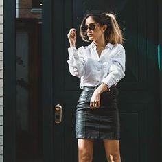 Look de Isaybela, usando camisa blanca y falda negra de vinil.
