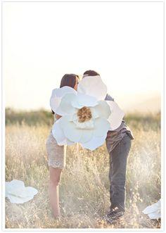 Such a cute engagement photo with a paper orchid prop! From http://100layercake.com/blog/2012/11/09/pastel-engagement-shoot/  Photo Credit: http://jana-williams.com/  Paper Flower by http://fleuretica.com/