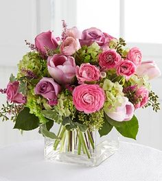 lavender roses, green hydrangea, pink ranunculus and pink tulips, lavender heather, English ivy and seeded eucalyptus.