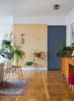 A entrada do apartamento ganhou painel de compensado com ganchos do mesmo material. Na frente, algumas espécies de plantas.