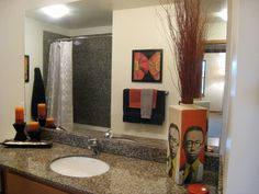 Flashy pop art and red decor complement the gray granite shower and vanity countertop in this bathroom. The large mirror over the vanity enlarges the otherwise small space.