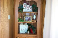 The corner cabinet made by my husband holds my most prized Christmas decoration - the three Santas painted on old fence boards bought years ago at a craft show in Big Spring, Texas.  The details in their faces are amazing.