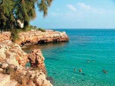 Locals and tourists enjoy the waters of Cala Marlonda in the Spanish resort city of Majorca.