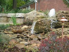 Omaha backyard landscape featuring a bubbling rock and waterfall from Lanoha Nurseries