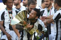 "Juventus Defender from Brazil Dani Alves celebrates with the trophy after winning the Italian Serie A football match Juventus vs Crotone and the ""Scudetto"" at the Juventus Stadium in Turin on May 21, 2017. First-half goals from Mario Mandzukic and Paulo Dybala, and a late header from Alex Sandro sealed a 3-0 win over Crotone to hand Juventus a record sixth consecutive Serie A title today. / AFP PHOTO / Filippo MONTEFORTE"