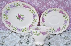 Vintage bone china tea trio made by English china company Tuscan, likely manufacture date 1950s The trio consists of tea cup, saucer, tea plate which are decorated with a design featuring sprays of lilac blossoms. The china is further enhanced with gilding to the edges of the pieces, handle and foot of cup and a border of filigree gilding. The china is in excellent vintage condition free from chips, cracks, crazing, stains and the gilding is still bright. As with all vintage items age and…