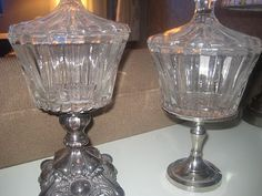 A $2 glass jar glued on top of 1. Silver candlestick holder 2.$8 candle holder from Micheal's.  Purty cool!
