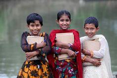 """Nupur, Iti e Hasy são alunas de 8 anos da 3ª série em um barco escolar na aldeia de Nasiarkandi em Bangladesh.  """"A escola chega até nós e gostamos de embarcar e aprender coisas novas"""", diz Iti. Aproximadamente 1.810 crianças frequentam aulas em 22 barcos escolares da ONG Shidhulai Swanirvar Sangstha em Bangladesh.  Fotografia: Abir Abdullah / Shidhulai Swanirvar Sangstha."""