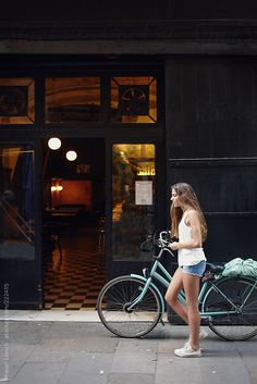 Young girl with bicycle in the old town of Barcelona city by Miquel Llonch for Stocksy United