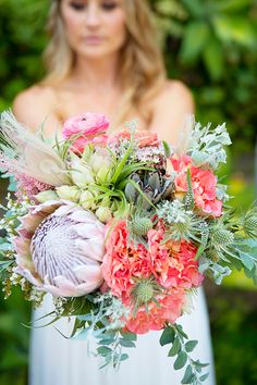gorgeous bright wedding bouquet full of proteas, thistles and even feathers!