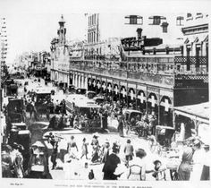 1903: Crowds of shoppers throng Smith Street, Collingwood in the area near Foy and Gibson's. Further down the street are Treadway's drapers, the post office, T. E. Jones bootshop and The Hall. Trams go in both directions, elegantly dressed women hurry back and forth across the road and the kerbs are lined with horses and carriages. The huge Foy and Gibson shop has an elaborate facade built over its verandah and dominates the streetscape.