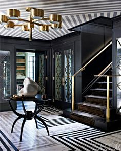 In an entry hall designed by Kelly Wearstler, the light fixture is vintage, and the stone sculpture is from JF Chen; the walls are painted in Glidden's Onyx Black, the floor is patterned with three different marbles and on the ceiling is a wall covering by SJW Studios.