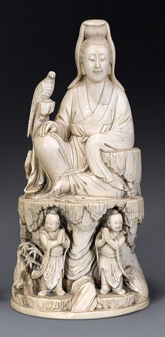 A carved ivory figure of Guanyin Qing dynasty, 18th/19th century  seated on a high rockwork ledge with right hand resting on her raised right knee, a long-tailed bird perched at her side, and with two boy attendants, their hands clasped in prayer standing below, with bamboo and flowering plants growing from crevices 23 cm high