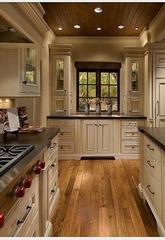 Elegant but homey kitchen with vanilla bean colored cabinets mixed with warm wood tones in the floor and ceiling.