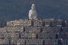 A 76-meter-high (249-feet) bronze-forged white Buddhist Avalokitesvara or Guan Yin statue, part of the Tsz Shan Monastery, stands behind luxurious houses at Taipo district in Hong Kong, April 16, 2015. The monastery, officially opened to the public by reservation on April 15, 2015, received contribution of HK$1.7 billion ($219 million) from Hong Kong tycoon Li Ka-shing's personal foundation to cover the construction and daily..