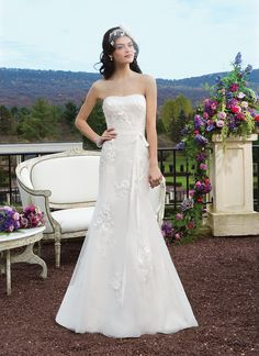 Sincerity wedding dress style 3815 Beaded and embroidered fit and flare gown featuring satin laser cut  flowers over tulle and a soft sweetheart neckline. The gown is finished  with a sized grosgrain detachable belt, satin covered buttons over the  back zipper and a chapel length train.