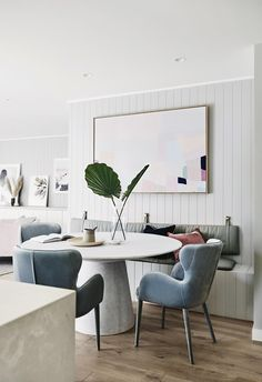 This Scandi-style dining area features a built-in bench to save space, accompanying velvet blue chairs and a circular dining table. | This renovated family home is a lesson in perfecting Scandi style | Inside Out - July 2018 | Styling: Nat Wheeler | Photography: Lisa Cohen