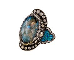 Sevan Bicakci Fluttering Dove Ring USD 17,727.00. The meticulously crafted dove has been created by intaglio carving into the underside of the oval smoky topaz. Painted to precision, the flutter of wings and feathers are encased in the pale stone which is framed by a meticulously detailed setting of clear diamonds, a few fancy yellow diamonds and larger rose cut diamonds in oxidized sterling silver. Two areas of blue and green patina connect the center composition to the wide band of 24K…