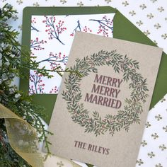 """#holiday card by @engagingpapers This holiday card features a watercolor #wreath print that hugs the words merry, merry, married""""."""