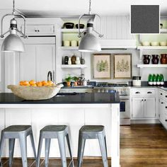 This slate-gray quartz countertop from Cambria has a muted, lived-in look to match the zinc stools and the weather-beaten-steel pendant light. Open shelves and painted cabinets with bin-pull drawer hardware add to the kitchen's homey appeal. | Photo: Wendell T. Webber | thisoldhouse.com