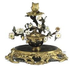 A LOUIS XV ORMOLU-MOUNTED CHINESE BLACK LACQUER, PORCELAIN AND TOLE PEINTE ENCRIER<br />MID-18TH CENTURY <br />With a bowl shaped ink-well on an oval platform with a flowering branch supporting a single foliate-cast candle sconce, on a base of pierced scrolled foliate and strapwork, the lacquer bowl possibly replacing a porcelain original<br />9½ in. (24 cm.) high; 11 in. (28 cm.) wide; 10 in. (26 cm.) deep <br />