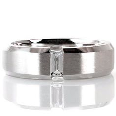 Design 1636 from Knox Jewelers is a men's wedding band featuring a 14k white gold band with a brushed finish and a .23ct emerald cut diamond.