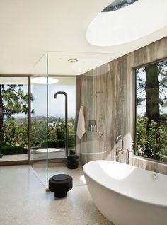 Une maison ronde par Dennis Gibbens Architects Berverly Hills salle de bain ouverte nature grande fenetre porte vitree et baie vitree baignoire ilot douche a l'italienne paroi en verre puis de lumière salle de douche design moderne