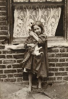 A young girl cuddles with a cat. [Spitalfields nippers: rare photographs of London street kids in 1901]   Credit: Horace Warner/The Religious Society of Friends in Britain A young girl cuddles with a cat
