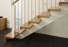 Spirit style staircase with L shaped riser and tread profile. Stainless steel spindles toppped with an oak handrail. More info - www.completestairsystems.co.uk/straight_stairs.html#Spirit