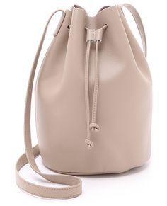 Drawstring bucket bag by Baggu. A smooth leather BAGGU bag with a drawstring bucket design. Adjustable shoulder straps. Unlined. ...