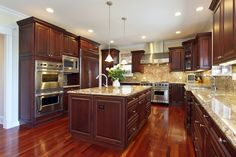 Large dark wood kitchen in luxury home. Kitchen opens up into living space and includes large central island with sink. Floor is wood and ceiling is white creating contrasting color scheme between dark kitchen design with light ceiling