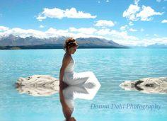Beautiful bride at Lake Pukaki, sitting on a rock with water reflection