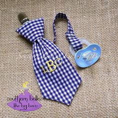 Your little man will look adorable and wont lose his pacifier with this stylish necktie pacifier clip that is personalized with an embroidered monogram! This makes a fabulous baby shower gift for a baby boy! Make it a gift and have a note included for no additional charge!  The necktie pictured is in a navy and white gingham print that is embroidered in yellow. Available in a variety of colors with a classic 3 letter monogram, 1 letter monogram or the full name (up to 7 letters). It is fully…