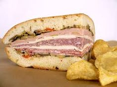 Muffuletta, both a type of round Sicilian sesame bread and a popular submarine-style sandwich originating among Italian immigrants in New Orleans. Best Sandwich, Sandwich Recipes, Snack Recipes, Snacks, Muffuletta Sandwich, Amazing Food Photography, Sammy, Delicious Burgers, Wrap Sandwiches