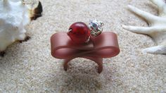Fereniki Handmade ring made of brown rubber, red glass bead and zircon.